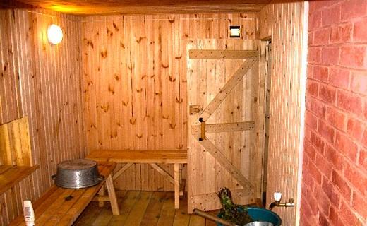 На снимке парилка в бане с деревянной дверью-