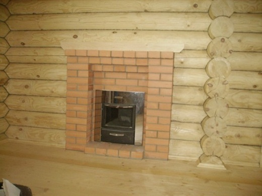 На фото представлен пример оформления топочной дверцы декоративным порталом, выполненным посредством кирпичной кладки.